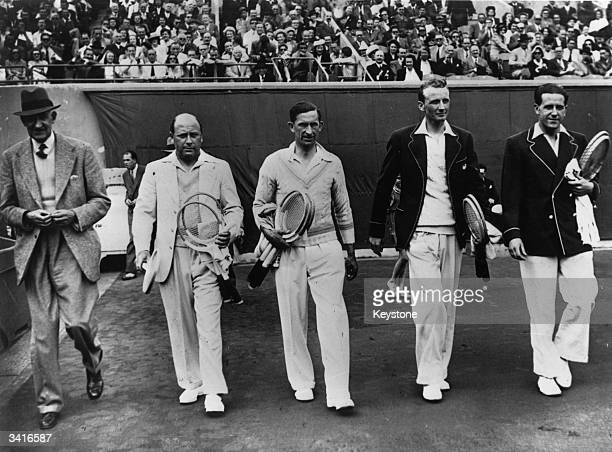 Marcel Bernard and Bernard Destremau of France walking on to the courts with Henry Billington and John Oliff of England before their Davis Cup...
