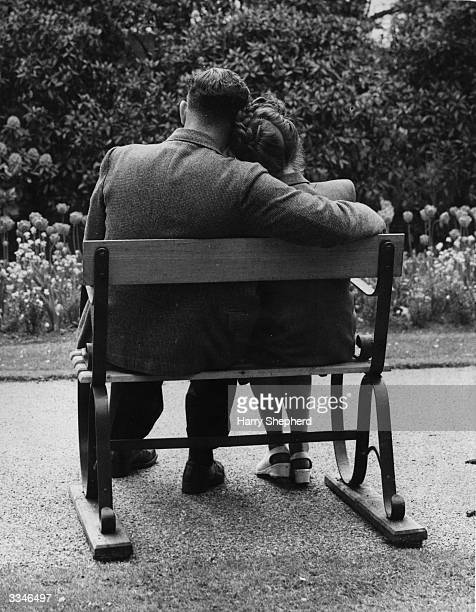 A couple trying out one of London County Council's new park benches which are made for two in Battersea Park
