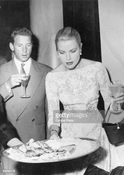 French film star Jean Pierre Aumont and American actress Grace Kelly survey the horsd'oeuvres at a reception in Cannes