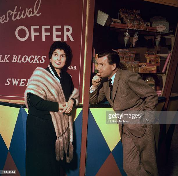 Film actor Kenneth More and English singer Alma Cogan attend the opening of the Festival Gardens at Battersea London