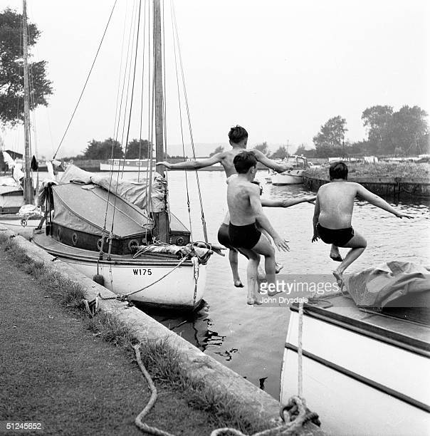 12th May 1957 A group of young boys take a flying leap into the water during a sailing holiday on the Norfolk Broads