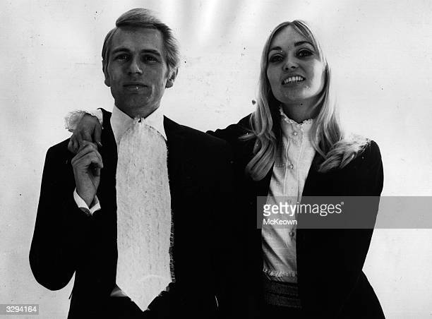 Pop singer and actor Adam Faith with his wife Jackie Irving modelling his and hers suits