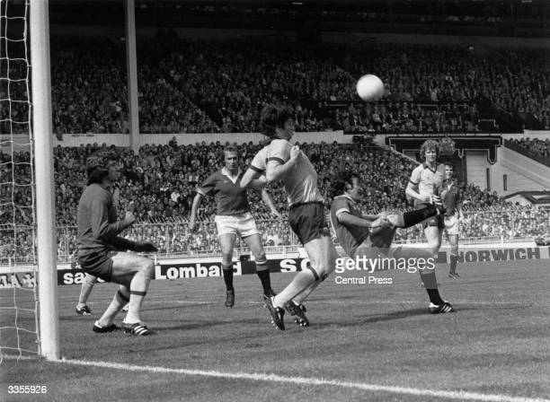 Lou Macari of Manchester United kicks the ball over Arsenal player Pat Rice and goalkeeper Pat Jennings during the 1979 FA Cup Final at Wembley...