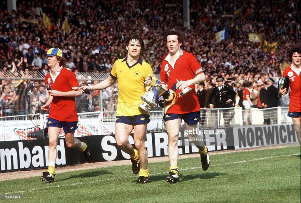 12th May 1979, Wembley, London, England, FA Cup Final, Arsenal 3 v Manchester United 2, Arsenal's Graham Rix, Pat Rice (yellow shirt) and Liam Brady celebrate with the trophy after their team won the FA Cup Final