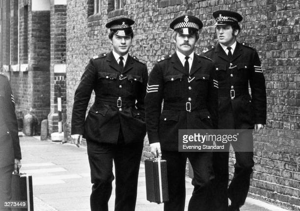 Three policemen on their way to court in Hammersmith London with evidence contained in a briefcase