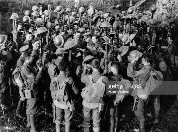Men of the First Battalion of Irish Guards hold aloft their steel helmets as they hear the news of the Armistice at Maubeuge in northern France