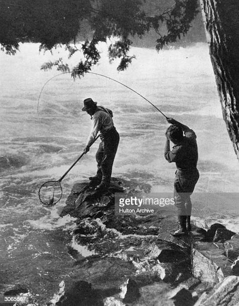 Two fishermen land a speckled trout on the Wipigon River Ontario Canada Original Publication Illustrated Sporting and Dramatic News pub 1927