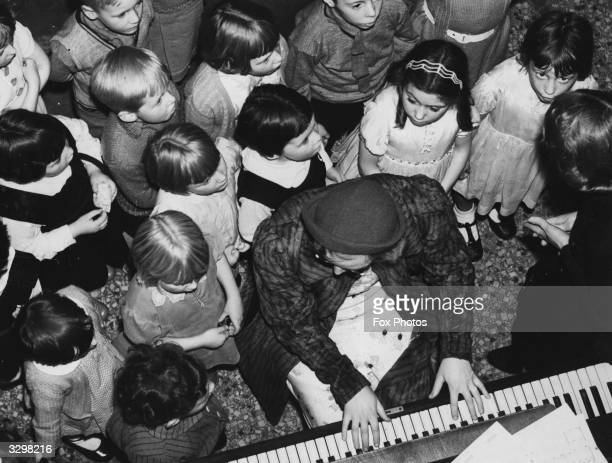 Children rehearsing for a Blackpool pantomime gathered round the piano player