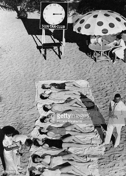 Members of the Miami Biltmore Country Club Sun Tan Club sunbathing for an hour under the supervision of a doctor and his attendants, at Coral Gables,...