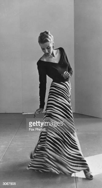 Holding a cigarette in a long holder Peggy Hunt models an evening dress with longsleeved vneck top and full length zebra print skirt