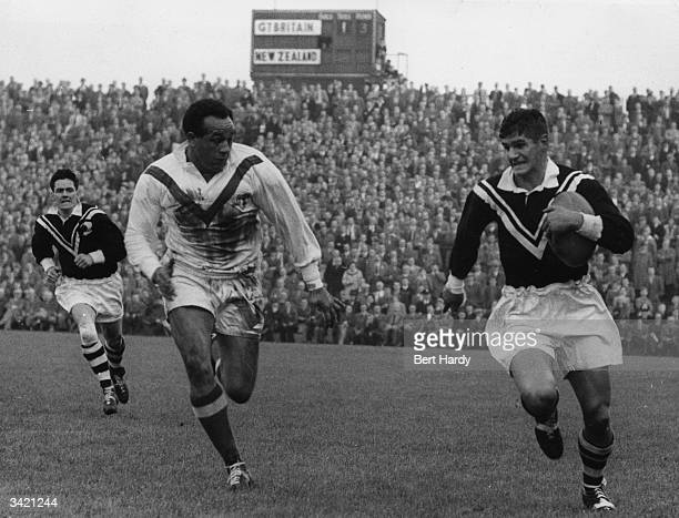 A New Zealand player chasing Britain's W Boston in possession of the ball during a Rugby League match at Swinton Original Publication Picture Post...