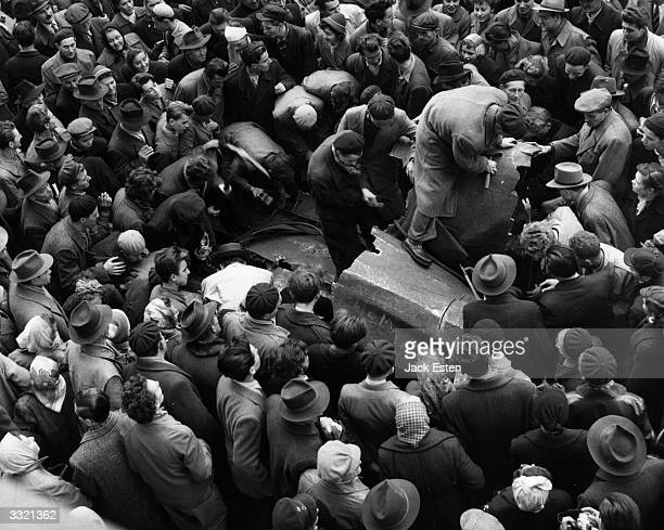 A crowd destroying a statue of Joseph Stalin during the anticommunist revolution in Hungary Original Publication Picture Post 8730 Hungary's Last...