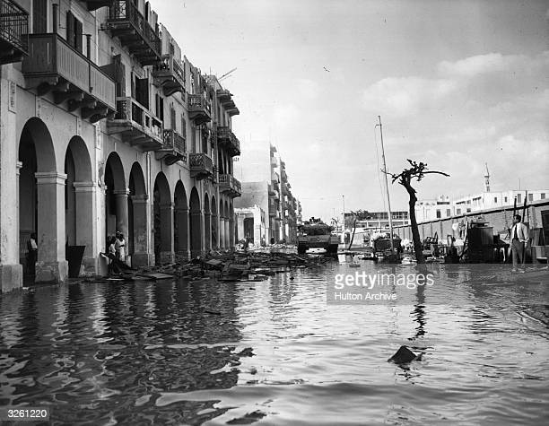 A flooded street in Egypt during the Suez Crisis A British tank stands guard
