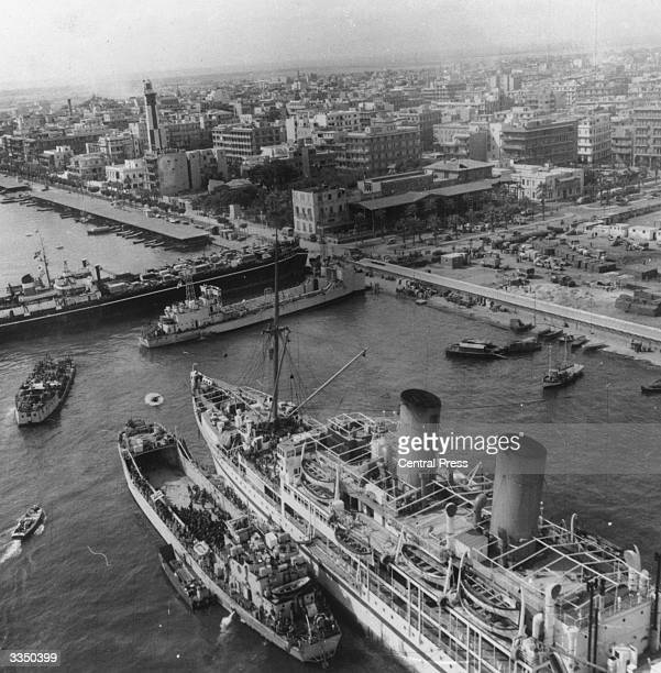 British reinforcements arriving on board the troopship Empire Ken and other landing craft at Port Said a port on the Mediterranean Sea at the...