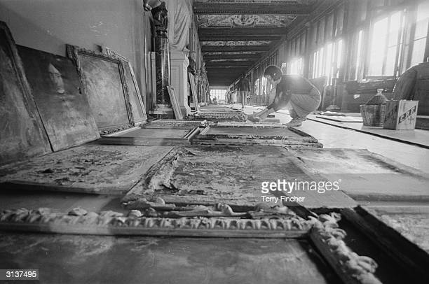 An art restorer examing paintings in need of restoration after flooding at the Uffizi Gallery in Florence