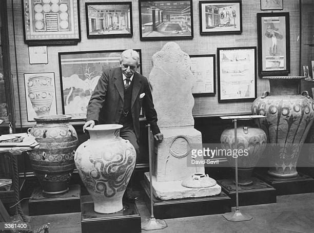 Sir Arthur Evans with a collection of Cretan exhibits at the Royal Academy Exhibition of Greek Antiquities He is leaning on a model of the Throne of...