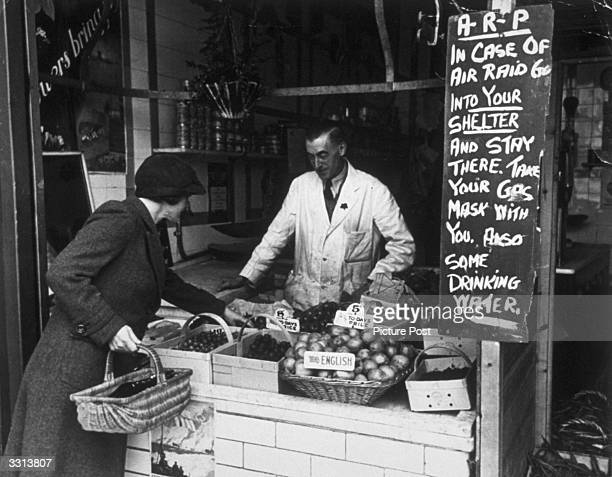 A greengrocer displaying an air raid precaution information sign Original Publication Picture Post 548 Munition Worker pub 1940