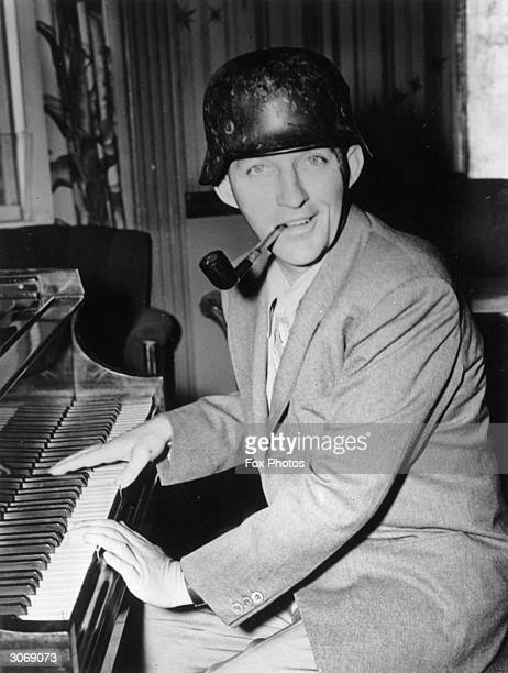 American entertainer Bing Crosby playing the piano and wearing a German helmet