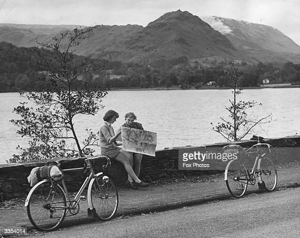 Margaret Blackburn and Vera Thompson resting to consult the map next to Grasmere during an Autumn holiday in the Lake District Cumbria