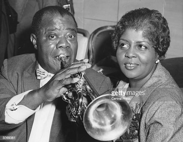 Louis 'Satchmo' Armstrong the great jazz trumpeter and vocalist plays a few notes at a press conference in London while his wife Lucille looks on...