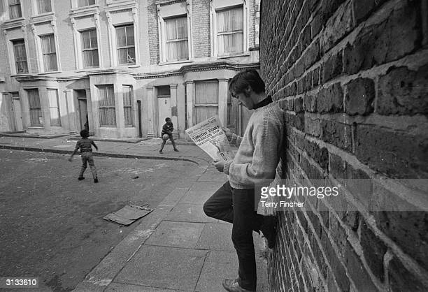 David King a former neighbour of murderer John Christie reading a newspaper while two children play football outside 10 Rillington Place London...