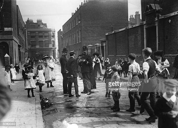 The ringleaders of the Shoreditch schoolboys' strike waiting outside Bath Street School for students to come out Two policemen and a phoptographer...