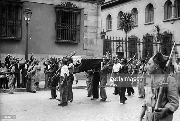 Members of the Republican militia forming a guard of honour as they carry the coffin of a female militia soldier through the streets of Madrid