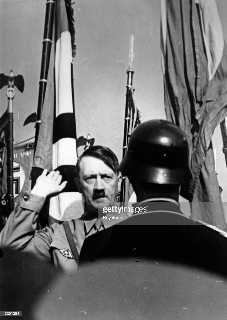 Adolf Hitler (1889 - 1945) the German dictator saluting guards at the Nuremberg Congress.