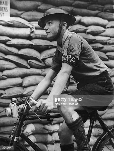 A boy scout working as an ARP warden carries a message by bicycle during the first week of the Second World War