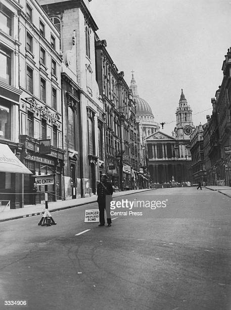 An air raid warden stands on duty in the middle of Ludgate Hill London sealed off to traffic on account of an unexploded bomb believed to be in the...