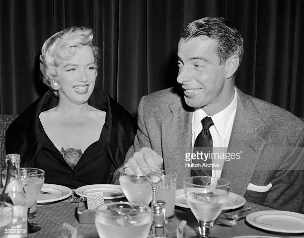 A portrait of Marilyn Monroe sitting with her husband Joe DiMaggio at El Morocco New York City New York