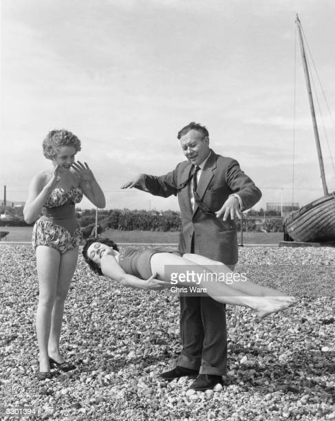 Magician Robert Harbin demonstrates one of his levitation tricks to a couple of sunbathers on the beach at Eastbourne