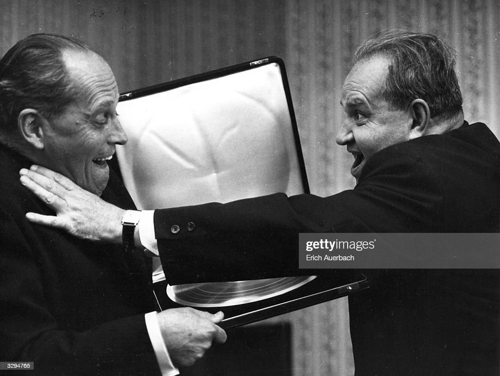 Jean Roire (left), presents the Russian violinist David Oistrakh (1908 - 1974), with a golden disc on his 60th birthday.