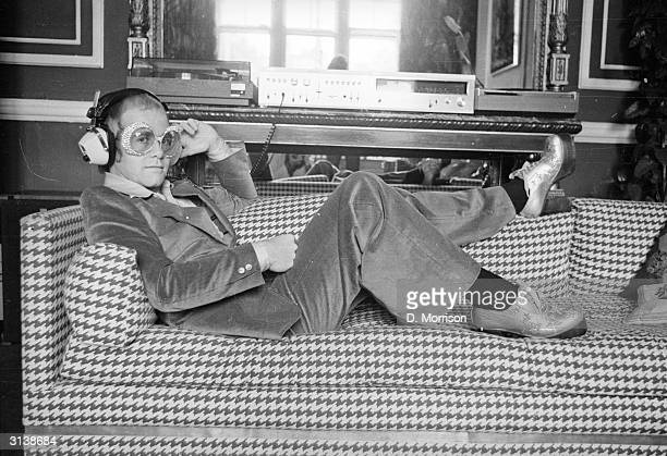 English pop star Elton John relaxes on a sofa and listens to some music