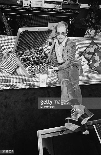 English pop star Elton John with a suitcase of his trademark sunglasses