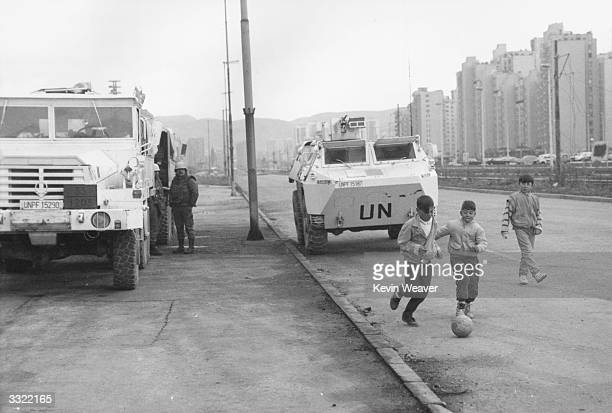 Children playing football beside UN vehicles parked at Sarajevo during civil war in Yugoslavia.