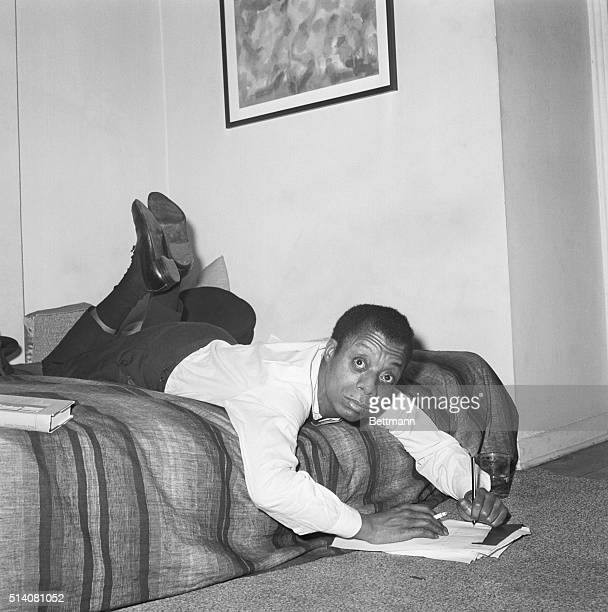 1/30/1963New York NY In a writing position that doesn't appear to be comfortable but really is novelist James Baldwin sprawls across the bed in his...