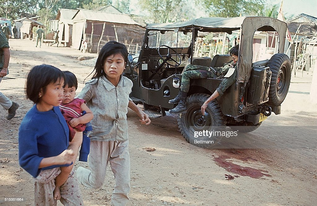 Girls Run Past Dead Soldier in Jeep : News Photo