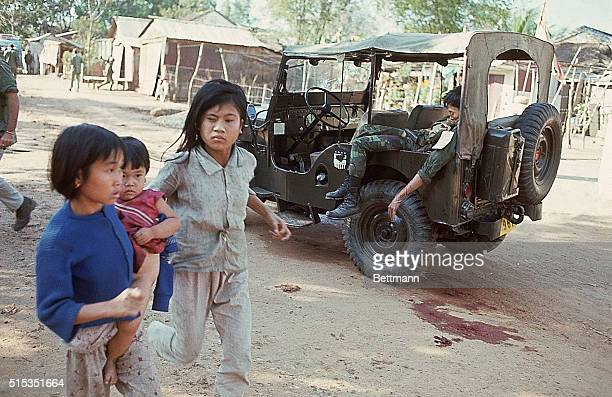 1/30/1968Da Nang South Vietnam Two young girls one carryng an infant run past a Jeep where a South Vietnamese soldier is slumped as street fighting...