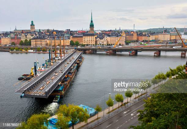 Ton and 200 meter long steel bridge is floated into place, where it will connect Stockholm's old town island to the southern city island Sodermalm,...