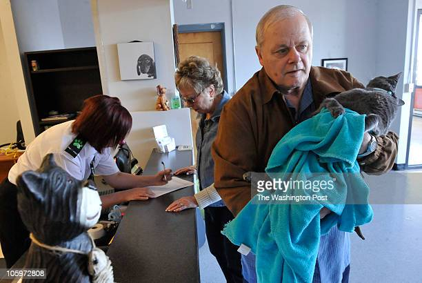 Jack Kenneycarried Dusty to a carrier as Carol Wilkins goes over paperwork with Brenda Mooreof Pet Airways for the cat's flight to Fort Lauderdale Fl...