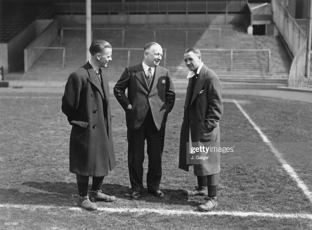 Arsenal Football Club Manager Herbert Chapman (centre), chats with a key member of his team , Alex James (right), on the pitch at Wembley before the FA Cup final.