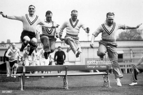 Warwickshire cricketers leaping over a bench