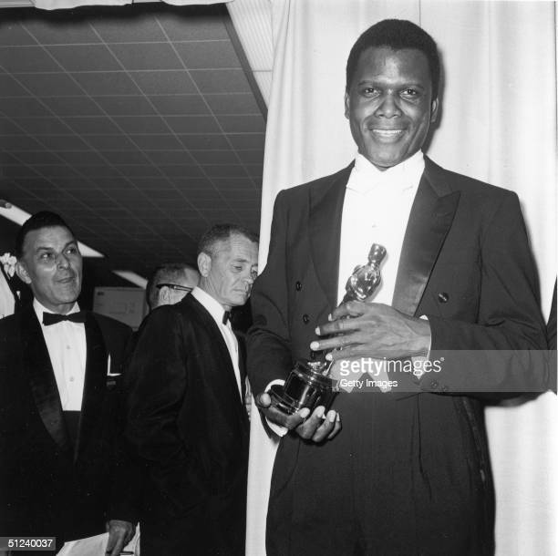 13th April 1964 American actor Sidney Poitier holds his Best Actor Oscar for director Ralph Nelson's film 'Lilies of The Field' backstage at the...