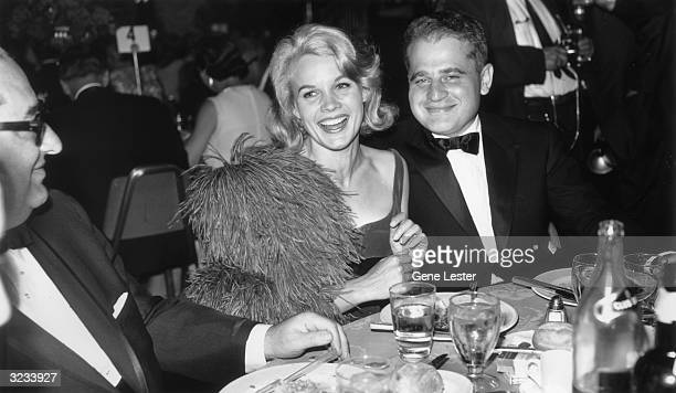 EXCLUSIVE American actor Carroll Baker laughs while sitting with her husband Czechoslovakianborn film director Jack Garfein at a banquet table during...