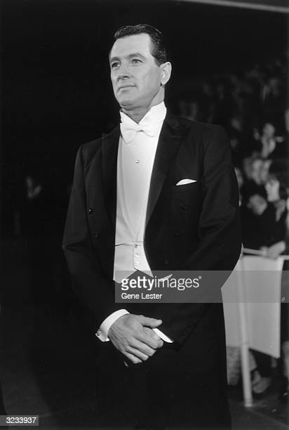 EXCLUSIVE American actor Rock Hudson smiles in white tie and tails at the Academy Awards Santa Monica California Crowds sit in the bleachers behind...