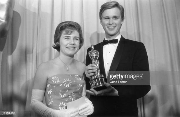 American actors Patty Duke and Brandon De Wilde smile and pose with an Oscar statuette and an envelope while serving as presenters backstage at the...