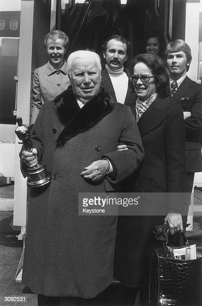 English film actor and director Charlie Chaplin holding the Oscar he received in Hollywood with his wife Oona after arriving at London Airport England