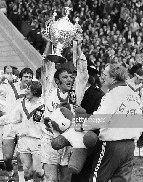 Hot and sweaty St Helens' captain Kelvin Coslett holds up the Rugby League cup after his team beat Leeds 16 13 at Wembley stadium in London A trainer...