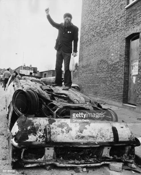 A man holds up his fist giving the Black Power salute and sticking his tongue out in defiance as he stands on top of an overturned burntout car which...